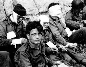 """Le 6 juin 1944, secteur Fox Green (Omaha Beach) à l'est de Colleville sur Mer,  des hommes du 3/16th RCT de la 1st US ID. Un centre de secours a été aménagé par le 6th Naval Beach Battalion dès H+50 au pied de la falaise, Le soldat qui regarde le photographe est Nicholas FINA, Compagnie """"I"""", il était toujours vivant en septembre 2006 et habitait Brooklyn, New York. Selon une autre source il s'agirait du matelot John Gallagher du 6th Naval Beach Bn. http://www.flickr.com/photos/mlq/4106484878/sizes/o/ Le dernier soldat à droite de la photo (hors cadre) avec la lettre E dans le dos est le Staff Sergeant Melvin L. Flammia de Richmond, Virginie du 116h IR de la 29th US ID.  D'après un de ses neveux, Bob Olsen, la péniche de débarquement dans laquelle il se trouvait a dérivé et elle s'est retrouvée dans ce secteur. Il est mort à Saint-Lô. Photo du correspondant de guerre Taylor Cette photo illustre la pochette du disque """"Rag Men"""" (hard rock): www.amazon.com/o/ASIN/B0001AD592  voir le reportage: p011341, p012524, p012901, p012908, p012914 et p012976."""